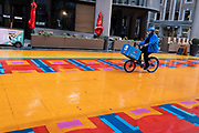 A Domino's pizza delivery courier rides his bike across a multicoloured pedestrianised traffic-free street in the City of London, capital's financial district, aka The Square Mile, on 20th October 2021, in London, England.