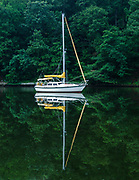 Sailboat mirrored on calm waters.