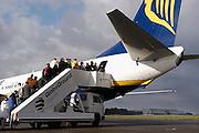 Duitsland, Laarbruch, 1-5-2003..Passagiers betreden een charter vliegtuig op de per 1-5-2003 in bedrijf gesteld airport Niederrhein. Vlak over de grens in Bergen N-Limburg vreest men voor geluidsoverlast. Drie keer per dag vliegt prijsbreker charter vliegmaatschappij Ryanair op Londen. Ook verwacht men veel lucht vrachtvervoer. Over twee maanden is de terminal klaar. Tot dan is aankomst en vertrek in de toekomstige hangar...Luchtvaart , economie, milieu, grensstreek, toerisme...Foto: Flip Franssen