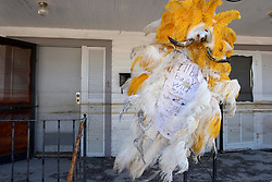 25 Oct,  2005. New Orleans, Louisiana.  Hurricane Katrina aftermath. <br /> The 8th ward lies in ruins following Katrina's devastating floods. The fabulous, somewhat dishevelled Mardi Gras Indian headress of Wild Man Loco is pinned defiantly to the outside of his home, clearly stating that 'I'll be back.'<br /> Photo; ©Charlie Varley/varleypix.com