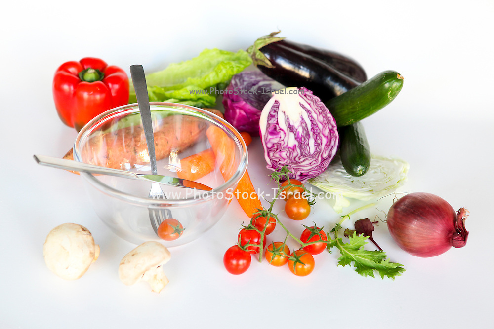 Fresh vegetables and an empty salad bowl. Whole uncut salad ingredients on white background