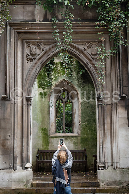 A woman taking a photo on a mobile phone at St Dunstan's in the East on the 20th September 2019 in London in the United Kingdom. St Dunstan's in the East was a Church of England parish church on St Dunstans Hill. The church was largely destroyed in the Second World War and the ruins are now a public garden.