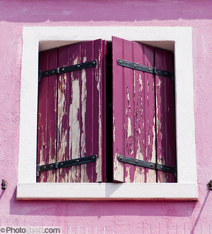 """Pink window shutters. Burano, known for knitted lacework, fishing, and colorfully painted houses, is a small archipelago of four islands linked by bridges in the Venetian Lagoon, northern Italy, Europe. Burano's traditional house colors are strictly regulated by government. The Romans may have been first to settle Burano. Romantic Venice (Venezia), """"City of Canals,"""" stretches across 117 small islands in the marshy Venetian Lagoon along the Adriatic Sea in northeast Italy, between the mouths of the Po (south) and Piave (north) Rivers. Venice and the Venetian Lagoons are on the prestigious UNESCO World Heritage List."""