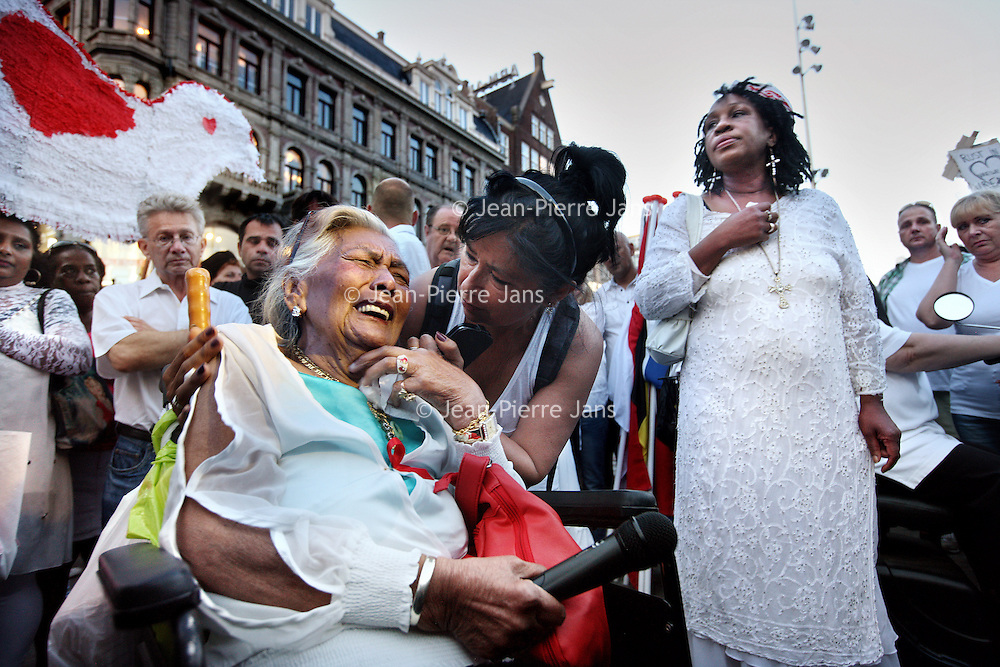 Nederland, Amsterdam , 23 juli 2014.<br /> Duizenden mensen lopen mee met een stille tocht door het centrum van Amsterdam. Volgens de organisatie zijn er zo'n vijfduizend deelnemers, meldt persbureau Novum. De wandeling begon om 20.00 uur op de Dam en eindigt daar ook weer. Deelnemers zullen daar witte ballonnen oplaten. Ook dragen zij witte kleding.<br /> <br /> Op de foto: Nabestaande oude vrouw rouwt op de Dam vanwege het verlies van 2 familieleden.<br /> <br /> Thousands of people in white clothes walk along with a silent march through the center of Amsterdam. The victims of flight MH17 are thus commemorated. National day of Mourning .