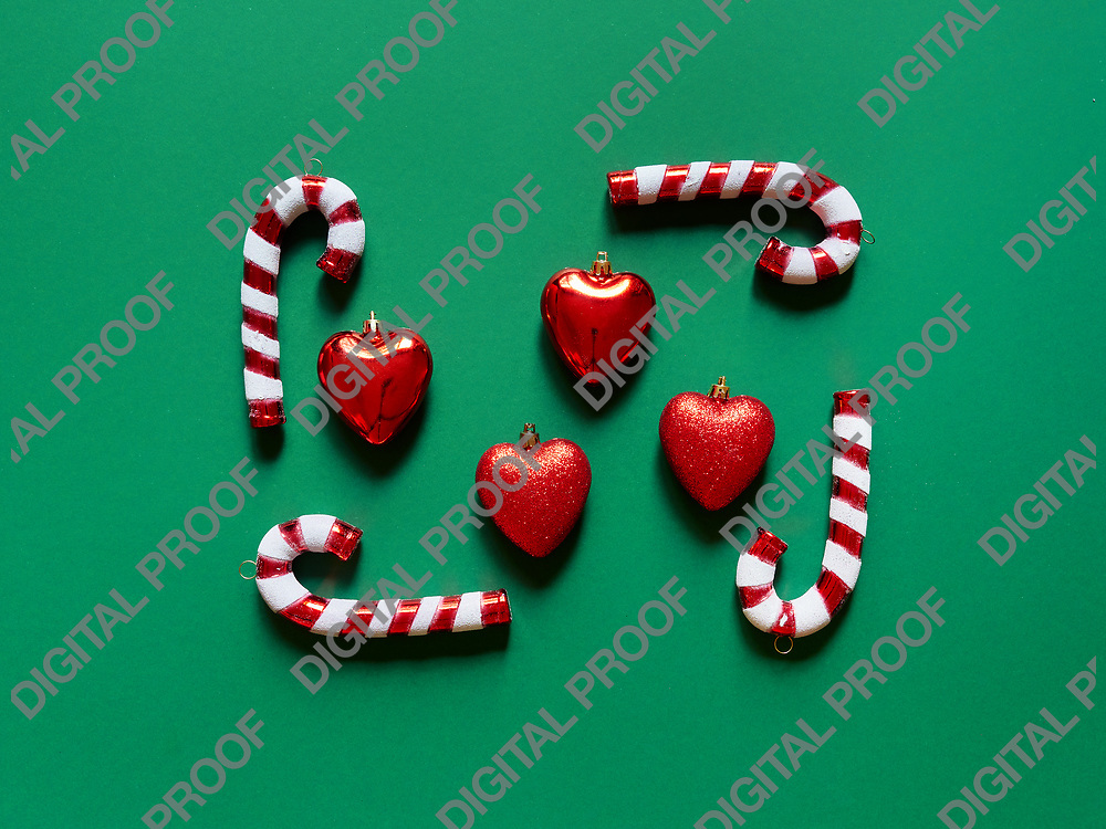 Christmas candy cane and hearts at studio above view over a green background isolated flatlay