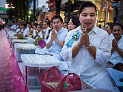 08 SEPTEMBER 2013 - BANGKOK, THAILAND:  People pray during a mass alms giving ceremony in Bangkok. 10,000 Buddhist monks participated in a mass alms giving ceremony on Rajadamri Road in front of Central World shopping mall in Bangkok. The alms giving was to benefit disaster victims in Thailand and assist Buddhist temples in the insurgency wracked southern provinces of Thailand.      PHOTO BY JACK KURTZ