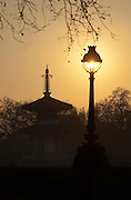 An old bandstand and street light silhouetted again a low sun in London, UK