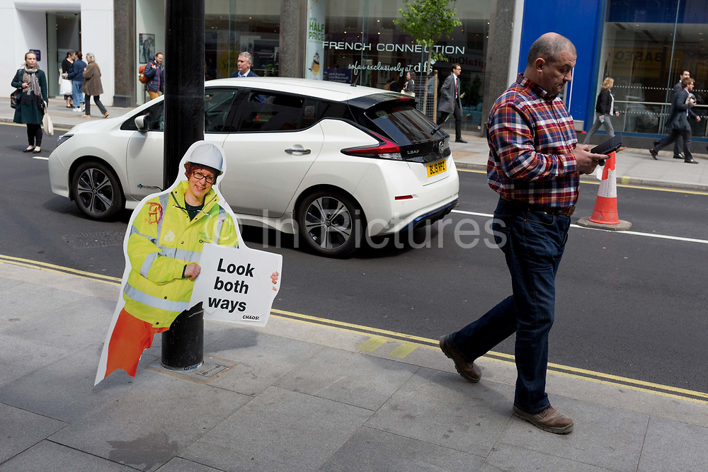 A pedestrian distracted with his mobile phone walks past a broken warning construction work figure - one of many up and down both sides of the Tottenham Court Road, warns pedestrians of a change of road layout, from one-way to two-way traffic, on 7th May 2019, in London, England.