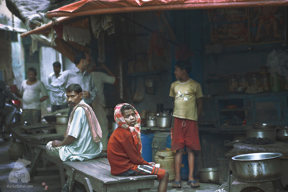 Patrons at a small 'Burrabazar' tea stall in Kolkata, West Bengal, India. While Burrabazar is often associated with the textile trade, it has become one of India's largest wholesale markets with more than 50,000 shops.