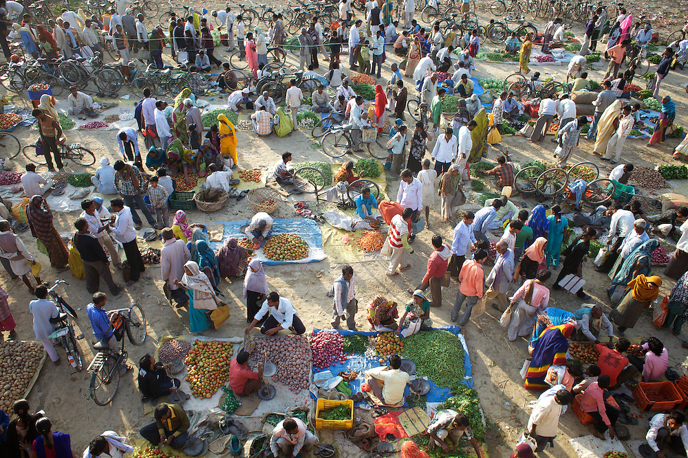 A twice-weekly vegetable market in the town of Bara Gaon. The price of staple foods including rice and vegetables has grown in India in recent months. Price rises in food always affects the poor who spend a greater proportion of their earnings on food than other groups. ..In the north Indian state of UP (Uttar Pradesh), women are responsible for 70 to 80 percent of agricultural work but their contribution remains neglected at all the levels: family, social, economic and policy. Over three quarters of UP's households are involved in farming of which 91% percent operate on land that is marginal and small. Small and marginal farmers often lack access to major agricultural services, such as credit, extension, insurance, and markets...On October 15, 2005 a movement called AROH was launched campaigning for the recognition of women as farmers. A federation of women farmers popularly known as Aroah Mahila Kissan Manch has been formed in all the districts of Uttar Pradesh. AROH has begun lobbying the UP government for women to be registered as joint owners - with their husbands - of land. At present only 6.5% of women own land in UP. AROH encourages womens co-operatives and other forms of group effort with the idea that these allow for the dissemination of information relating to agricultural technology and other inputs, as well as for the marketing of produce...AROH have found that public sector investments are declining in the agriculture sector. Given the number of women who rely on agricultural work in UP, this this declining investment is of grave concern to the campaign. ..Photo: Tom Pietrasik.Bara Gaon, Faizabad District, Uttar Pradesh. India.March 1st 2011