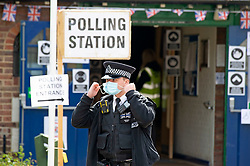 © Licensed to London News Pictures 06/05/2021. Bromley, UK. A police officer at Hayes Village Hall in Bromley, London. Local council Elections 2021. Polling stations have opened across the UK today to allow people to vote for their Local councillors, police and crime commissioners and Londoners will get to elect the next Mayor of London. Due to Coronavirus people have to wear masks when voting. Photo credit:Grant Falvey/LNP
