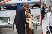 COUPLE AT THE TICKET MACHINE AFTER BUYING TICKETS FROM THE AUTOMATED TICKET MACHINES, Royal Ascot racegoers at Waterloo station. London. 19 June 2013.