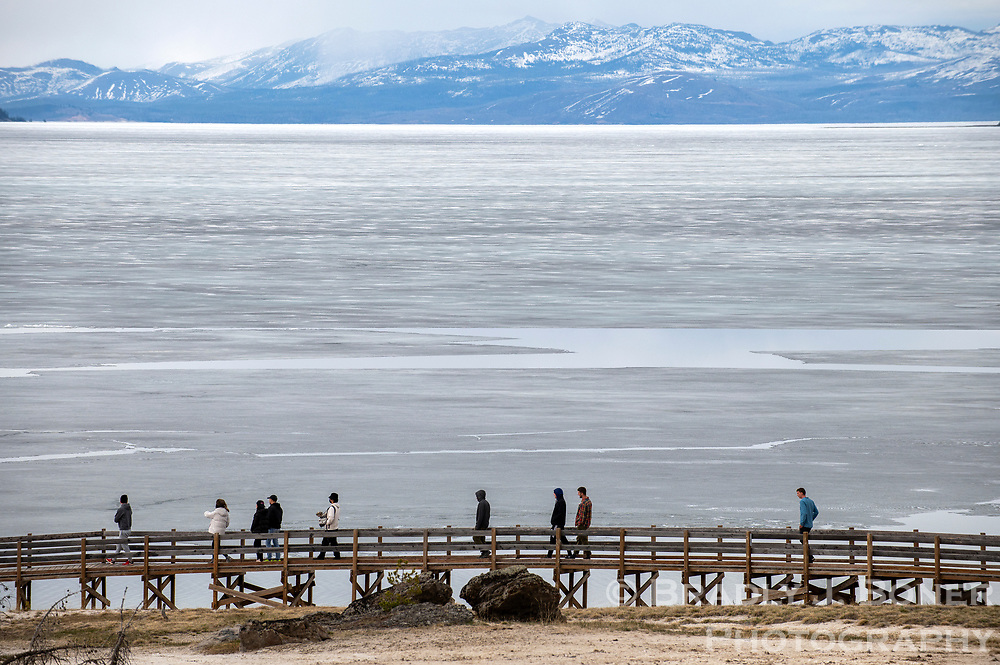 Tourists to Yellowstone Lake walk along the boardwalks at the West Thumb Geyser Basin next to a frozen Yellowstone Lake on Saturday. The South Entrance to the world's first national park opened last week as Yellowstone visitation begins to trickle in for the 2021 season.