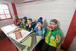 Children eating pepperoni pizza at restaurant