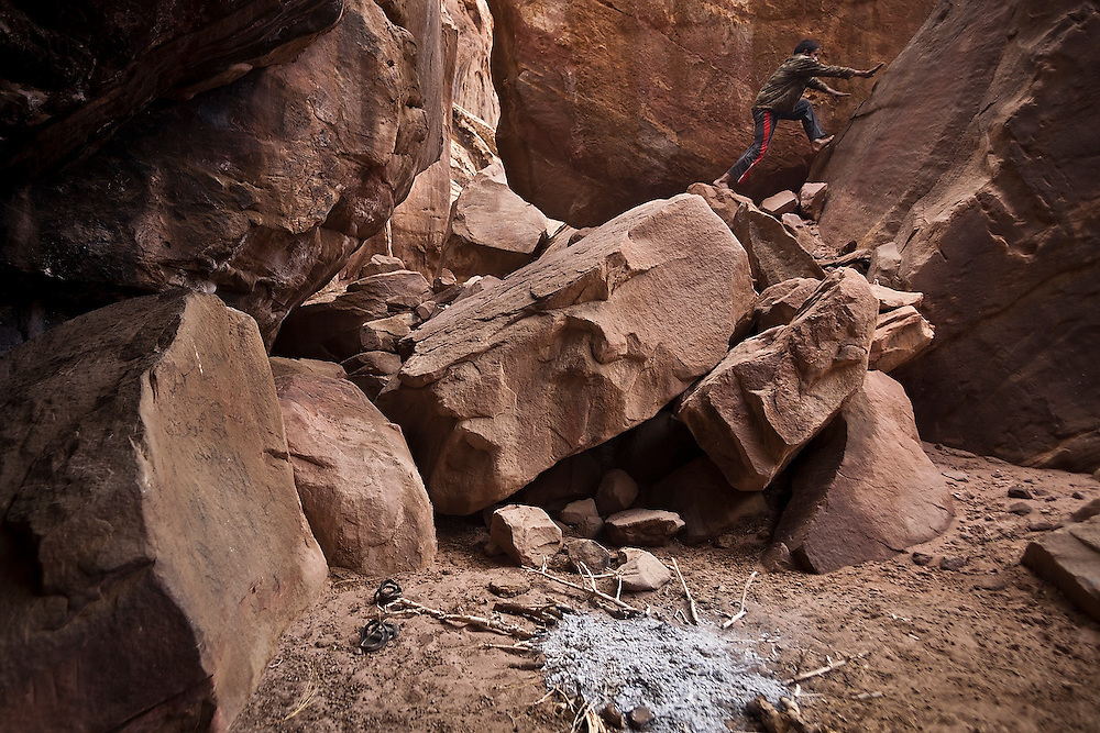 A Bedouin boy scrambles up large boulders above a campsite near his family's encampment in Wadi Rum, Jordan.
