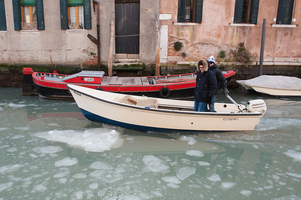 VENICE, ITALY - FEBRUARY 05:  Locals on a motor boat brave the weather sailing on a partially frozen canal on February 5, 2012 in Venice, Italy. Italy as most of Europe is under a spell of very cold weather, it is more than 20 years aince the Venice Lagoon last froze.  (Photo by Marco Secchi/Getty Images)
