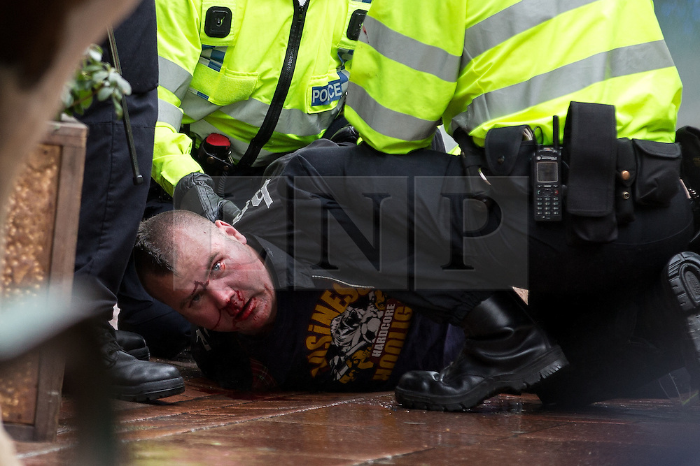 © Licensed to London News Pictures . 27/04/2014 . Brighton , UK . A bloodied man is detained after a fight in the street . Nationalist group March for England march in Brighton , timed to coincide with St George's Day. The annual event has resulted in open fighting between anti-fascist groups and right wing nationalists and injuries to police trying to separate opposing groups . Sussex Police reports their operation to manage the event costs £500,000 . Photo credit : Joel Goodman/LNP