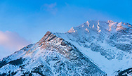 Winter sunrise colours and morning light on the snowy upper slope and summit of Mount McLaren in Alberta, Canada