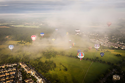 Balloons pass through cloud as they fill the skies of Bristol as dozens of balloon pilots take part in a mass launch from Clifton Downs to mark less than a week to go until the start of the Bristol International Balloon Fiesta.