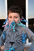 young boy playing with plastic clothing clips