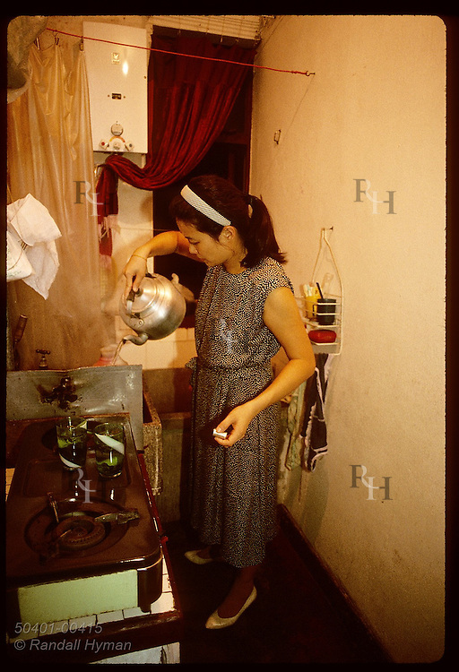 Housewife pours kettle of hot water in tiny kitchen of family's state-subsidized aprtmt;Shanghai China