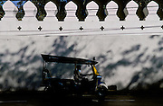 A tuk tuk motor rickshaw in front of the palace walls in Bangkok, Thailand. March 2001