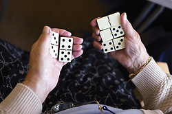 Close up of elderly woman's hands holding dominoes,