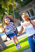Mom pushing daughter on the Swing at George Washington Park in Anaheim