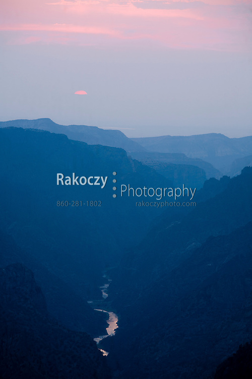 The setting sun, obscured by the haze, casts a last flash of pink on the clouds over the Black Canyon of the Gunnison.