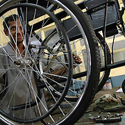 Ravi Chandran 'testing' a wheel chair under production in the manufacturing unit at APD. He suffers from polio and was trained at APD center as a welder and a fitter of orthotic appliances.