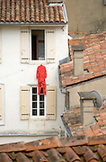 red overall hanging to dry from window sill