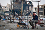 A young boy sells scraps of metal and plastic harvested from the wreckage of an appliance store next to the Al-Abrar Mosque in Rafah, Gaza Strip. The Israeli military destroyed the mosque with an airstrike because they said Hamas was using it as a weapons cache.