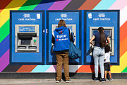 People make cash withdrawals from Halifax cash machines, or ATMs, set on a colourful wall on 26th August, 2021 in Manchester, United Kingdom. Many of the UKs high streets and shopping centres are bustling once again, welcoming shoppers back as footfall slowly climbs back to levels seen before the restrictions brought about by the Covid-19 pandemic.
