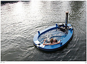 Full steam ahead! The 'Hot Tub' boat which can let you lazily cruise down the river in comfort<br /> <br /> There's almost nothing more luxuriously relaxing than taking a dip in a hot tub, except perhaps taking a slow cruise down a beautiful river.<br /> Now you can combine the best of both world - with a hot tub cruise thanks to an ambitious company in the Netherlands, which created the hybrid machine to provide the ultimate river journey.<br /> The 'Hot Tub', powered by a steam wood-burning stove to heat the water and a propeller engine to keep you sailing merrily down the stream.<br /> The boat contains up to 2,000litres of water and comes with either an integrated electric motor or an outboard model.<br /> If you cannot wait and are already getting the cheque-book out, be warned you may need a little more patience, as it will take three hours to get the water up to the required heat.<br /> <br /> The creators say the water can be 'as warm as you want, but average people find a comfortable temperature of 38C and that is no problem for the HotTug heater.'<br /> Available to rent or buy, the hot tub boat is made from wood and fitted with glass-fiber reinforced polyester, measuring 240cm by 380cm by 110 cm.<br /> <br /> When used as a regular boat, eight people can enjoy a sail. Add hot water to the mix, and six people can still enjoy a mobile bath.<br /> If you are just after the boat, without motors or a stove, you are looking at around £7,200. Throw in the stove and other equipment and the price is around £13,000.<br /> But if you happen to be the owner of a private lake, this might be affordable enough to give you a very unique hot tub experience.<br /> ©Hot Tug/Exclusivepix