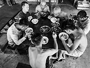 """15 FEBRUARY 2019 - SIHANOUKVILLE, CAMBODIA: Chinese construction workers eat lunch at the dining hall in the housing complex at which they live. There are about 80 Chinese casinos and resort hotels open in Sihanoukville and dozens more under construction. The casinos are changing the city, once a sleepy port on Southeast Asia's """"backpacker trail"""" into a booming city. The change is coming with a cost though. Many Cambodian residents of Sihanoukville  have lost their homes to make way for the casinos and the jobs are going to Chinese workers, brought in to build casinos and work in the casinos.      PHOTO BY JACK KURTZ"""