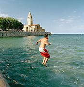 A boy jumps into the ocean by the church of San Pedro in Gijon, Asturais, Spain