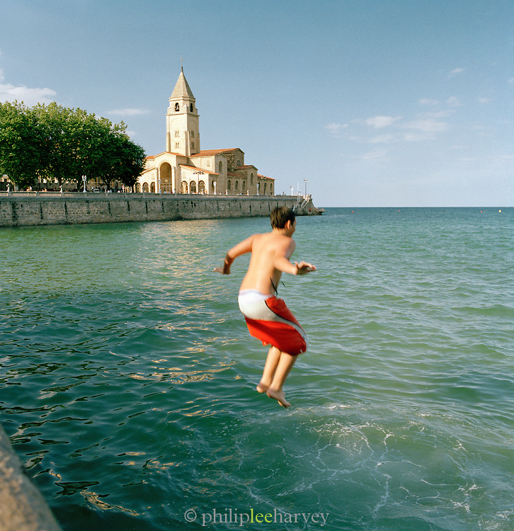 A boy jumps into the ocean by the church of San Pedro in Gijon, Asturais, Spain