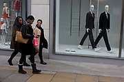 Three black girlfriends walk past odd mannequins in a central London street. Striding in rhythm with the shop window models, the women are enjoying their shopping trip to Oxford Street where the opportunities for retail therapy are far and wide. One smiles at a joke and another carries a pink bag from a nearby store. The mannequins are stylish and in step.