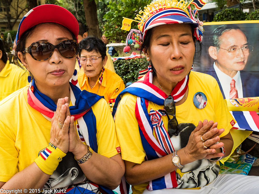 05 DECEMBER 2015 - BANGKOK, THAILAND: Women pray for the King in the plaza at Siriraj Hospital on the 88th birthday of Bhumibol Adulyadej, the King of Thailand. Hundreds of people crowded into the plaza hoping to catch a glimpse of the revered Monarch. The King has lived at Siriraj Hospital off and on for more than four years.     PHOTO BY JACK KURTZ