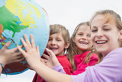 Brother and sisters holding globe balloon smiling