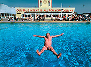 Man falling backwards into swimming pool in Butlins holiday camp, Skegness. The slogan Our true intent is all for your delight was borrowed from Midsummers Nights Dream. Butlins Skegness is a holiday camp located in Ingoldmells near Skegness in Lincolnshire. Sir William Butlin conceived of its creation based on his experiences at a Canadian summer camp in his youth and by observation of the actions of other holiday accommodation providers, both in seaside resort lodging houses and in earlier smaller holiday campsThe camp began opened in 1936, when it quickly proved to be a success with a need for expansion. The camp included dining and recreation facilities, such as dance halls and sports fields. Over the past 75 years the camp has seen continuous use and development, in the mid-1980s and again in the late 1990s being subject to substantial investment and redevelopment. In the late 1990s the site was re-branded as a holiday resort, and remains open today as one of three remaining Butlins resorts.