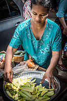 Woman on the streets of Yangon slicing up pieces of green mango to sell.