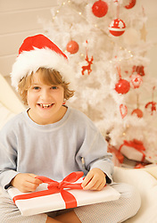 Boy sitting by Christmas tree in a red and white furry hat unwrapping a gift