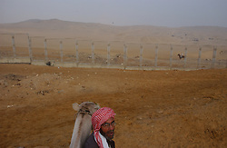 Cairo, Egpyt: An Egyptain man walks in the desert with a camel in Cairo, Egypt . (Photo Ami Vitale)