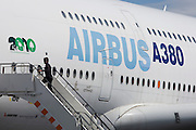 Airbus employee climbs steps of the comapny's A380 before the airliner's flying display at the Farnborough Airshow. The employee leaps up the last of the steps on to the first level of this double-decker jet airliner that is making its second visit to the the Farnborough International Airshow, a seven-day international trade fair for the aerospace business which is held biennially in Hampshire, England. The airshow is organised by Farnborough International Limited, a wholly owned subsidiary of British aerospace industry's body the Society of British Aerospace Companies (SBAC) to demonstrate both civilian and military aircraft to potential customers and investors.