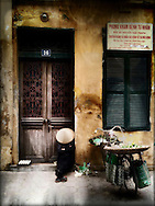 A street vendor takes a nap with a conical hat over her face in a street of Hanoi, Vietnam, Southeast Asia
