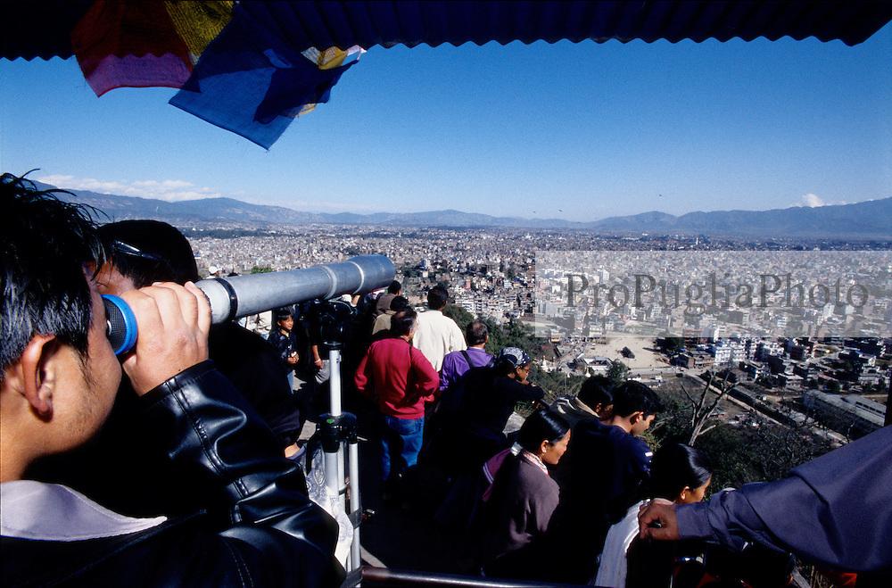 Kathmandu, 13n February 2005. Pilgrims looking Kathmandu through the lens from Swayambhunath Temple.