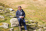 Woman sitting in countryside, Lake District national park, Cumbria, England, UK