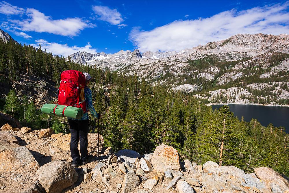 Backpacker above South Lake, John Muir Wilderness, Sierra Nevada Mountains, California USA