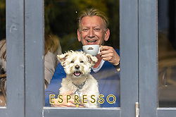 Licensed to London News Pictures. 17/05/2021. London, UK. At last. Andrew Borek from Wimbledon enjoys a coffee with his Westie-Poo, Molly, at a cafè in Wimbledon Village, south west London as the Government's roadmap out of lockdown continues with pubs, restaurants, cafes and bars able to serve customers inside. However Downing Street has warned that due to the Indian variant, local lockdowns could be quickly reintroduced in high risk areas. Photo credit: Alex Lentati/LNP
